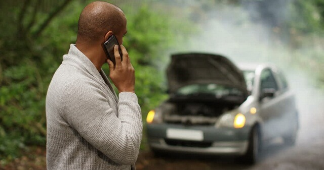 a frustrated person with his damaged car on the road