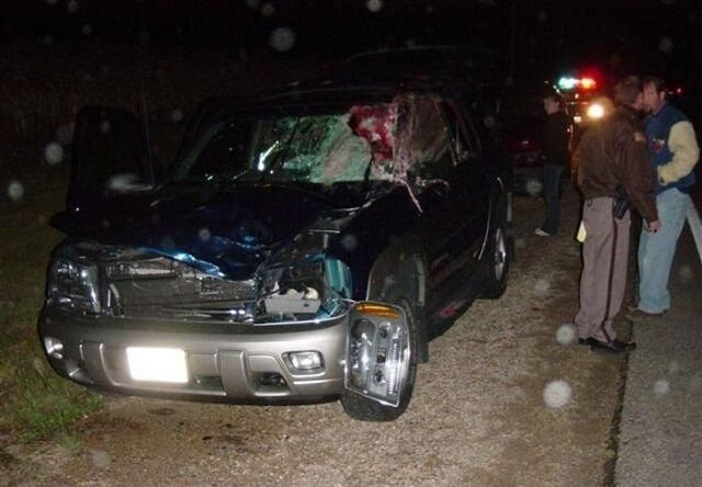 a person with his damaged car at night
